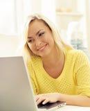 Glückliches blondes Mädchen mit Notizbuch zu Hause On-line-Einkaufen, Laptop Lizenzfreie Stockfotos
