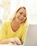 Glückliches blondes Mädchen mit Notizbuch zu Hause On-line-Einkaufen, Laptop Lizenzfreie Stockbilder