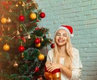 Glückliches blondes Mädchen mit Weihnachtsgeschenk beim Sankt-Hutlächeln Lizenzfreies Stockbild