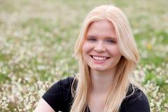 Glückliches blondes Mädchen umgeben durch Blumen Stockfotografie