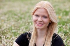 Glückliches blondes Mädchen umgeben durch Blumen Lizenzfreie Stockfotografie