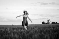 Glückliches blondes Mädchen, voll tanzend auf einem Gebiet von gelben Blumen Hintergrund der Sommerzeit und der blauen Himmel Stockfoto