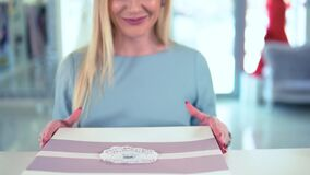 Glückliches blondes weibliches erhaltenes verpacktes Kaufeinzelteil am Register in der Luxusboutique stock footage
