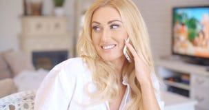 Glückliches blondes weibliches Nennen am Telefon, das nach links schaut Stockfotos