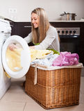 Glückliches Blondineladen kleidet in Waschmaschine Stockfotos