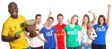 Glückliches brasilianisches Fußballfan mit Trommel und anderen Fans Stockbilder