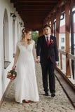 Glückliches Brauthändchenhalten mit Bräutigam, schöne blonde Braut herein Lizenzfreies Stockbild