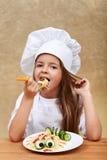 Glückliches Chefkind, das einen kreativen Teigwarenteller isst Stockbilder
