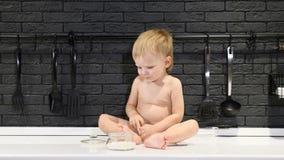 Glückliches chilhood Konzept Netter kleiner Junge, der auf der Tabelle schmeckt Zucker und Bonbons mit seinem Finger sitzt 4K stock footage