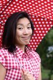 Glückliches chinesisches Mädchen mit punktiertem Regenschirm und Hemd stockfotografie
