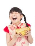 Glückliches chinesisches neues Jahr. kleines Mädchen, das Gold zeigt Stockfotografie