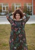 Glückliches curvy Mädchen mit dem gelockten Haar in der Straße, die ihr Haar berührt stockfotos