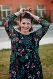 Glückliches curvy Mädchen mit dem gelockten Haar in der Straße, die ihr Haar berührt lizenzfreie stockfotografie