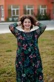 Glückliches curvy Mädchen mit dem gelockten Haar in der Straße, die ihr Haar berührt stockfotografie