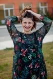 Glückliches curvy Mädchen mit dem gelockten Haar in der Straße, die ihr Haar berührt lizenzfreies stockbild