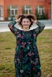 Glückliches curvy Mädchen mit dem gelockten Haar in der Straße, die ihr Haar berührt lizenzfreie stockbilder