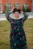Glückliches curvy Mädchen mit dem gelockten Haar in der Straße, die ihr Haar berührt lizenzfreie stockfotos