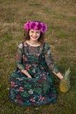Glückliches curvy Mädchen mit einer Ananas und eine Blume krönen stockfoto