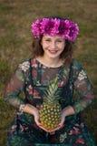 Glückliches curvy Mädchen mit einer Ananas und eine Blume krönen lizenzfreie stockbilder