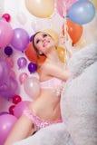 Glückliches dünnes Mädchen, das mit Bündel Ballonen aufwirft Stockbild