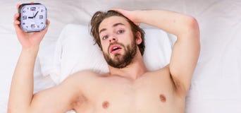 Glückliches in den steigenden Händen des Betts mit dem neuen Gefühl morgens aufwachen des faulen Mannes entspannt Mann, der zurüc stockfotografie