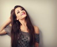 Glückliches denkendes junges weibliches Modell der Mode, das oben auf leerer Co schaut stockfotografie