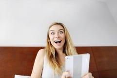 Glückliches der jungen Frau entsetzt mit der Tablette, die Kamera auf weißes Bett betrachtet Stockfoto