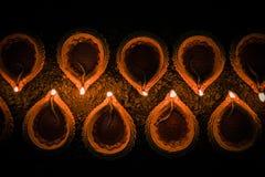 Glückliches Diwali -, das Terrakottadiya oder -öllampen vereinbart über Lehmoberfläche oder -boden in einer Linie oder gebogene o stockbild
