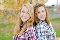 Zwei glückliche lächelnde jugendlich Schulfreundinnen draußen Stockbild