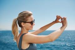 Glückliches Eignung selfie blondes Mädchen, das Selbstporträt nehmend lächelt Stockfoto