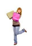 Glückliches Einkaufenmädchen auf einem Fahrwerkbein Lizenzfreies Stockfoto