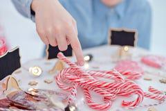 Glückliches Einkaufenmädchen auf weißem Hintergrund Kinder verkaufen Bonbons des neuen Jahres Glatte Karamellstöcke eco Bonbons Stockfotos