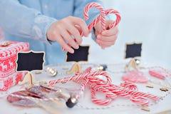 Glückliches Einkaufenmädchen auf weißem Hintergrund Kinder verkaufen Bonbons des neuen Jahres Glatte Karamellstöcke eco Bonbons Lizenzfreie Stockfotografie