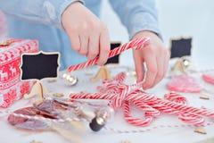 Glückliches Einkaufenmädchen auf weißem Hintergrund Kinder verkaufen Bonbons des neuen Jahres Glatte Karamellstöcke eco Bonbons Stockbild