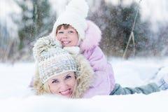 Glückliches Elternteil und Kind, die mit Schnee im Winter spielt Stockfotografie