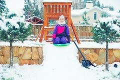 Glückliches emotionales Mädchenreiten auf Pflugsohle im Winterpark mit schneebedecktem Spielplatz Stockbild