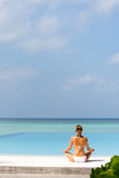 Glückliches entspanntes übendes Yoga der jungen Frau draußen am weißen Strand Lizenzfreie Stockfotografie