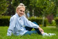 Glückliches entspanntes Studentenmädchen, das auf grünem Gras sitzt Stockfotografie