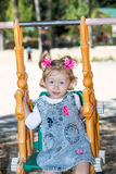 Glückliches entzückendes Kindermädchen auf Schwingen auf Spielplatz nahe Kindergarten Montessori auf Sommer Stockfoto