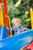 Glückliches entzückendes Mädchen auf dem Dia der Kinder auf Spielplatz nahe Kindergarten Montessori Lizenzfreie Stockfotos