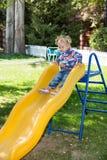Glückliches entzückendes Mädchen auf dem Dia der Kinder auf Spielplatz nahe Kindergarten Montessori auf Sommer Lizenzfreie Stockfotos