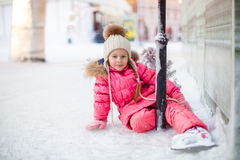 Glückliches entzückendes Mädchen, das auf Eis mit Rochen sitzt Stockbilder