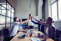 Glückliches erfolgreiches gemischtrassiges Geschäftsteam, das eine Hoch fives Geste gibt, wie sie ihren Erfolg lachen und zujubel lizenzfreies stockbild