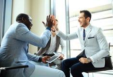 Glückliches erfolgreiches gemischtrassiges Geschäftsteam, das eine Hoch fives Geste gibt, wie sie ihren Erfolg lachen und zujubel stockfotografie