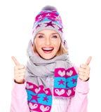 Glückliches erwachsenes Mädchen im Winter kleidet mit den Daumen oben Stockbilder