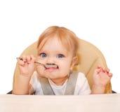 Glückliches essendes Baby in einem Hochstuhl Stockfotos