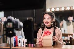 Glückliches führendes Blog der jungen Frau über kosmetische Geschenke Lizenzfreie Stockbilder