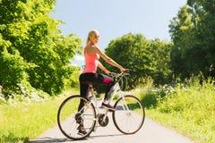 Glückliches Fahrrad der jungen Frau Reitdraußen stockfotografie