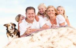 Glückliches Familien-und Hundeportrait am Strand Stockfotos