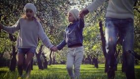 Glückliches Familienhändchenhalten, das in den Park geht stock video